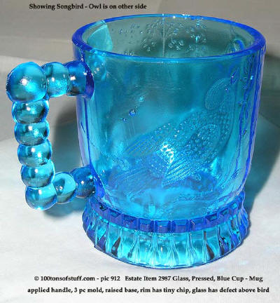 100tos#2987 Side & mouth view of blue glass cup w/embossed design of songbirg & owl & tree.