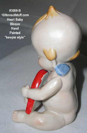 3009B - other side of pottery Kewpie showing red heart and blue wings